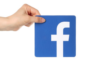 KIEV UKRAINE - APRIL 30 2015: Hand holds facebook logo printed on paper on white background. Facebook is a well-known social networking service.
